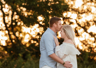 Couple embrace as sun goes down behind trees