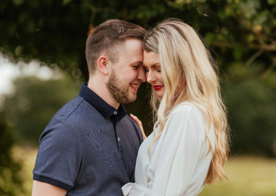 Groom head leans on brides intimate engagement session moment