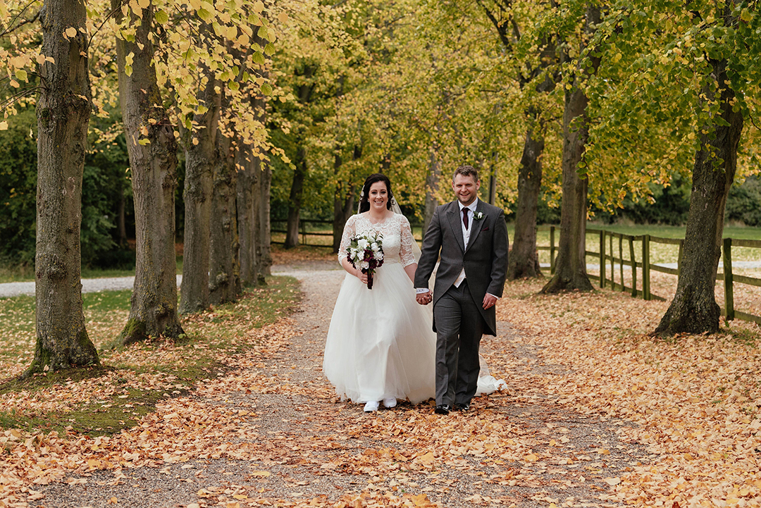 Bride and groom walk towards camera in autumnal couples shot at Colville Hall