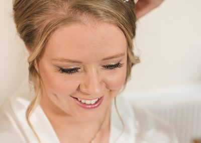 Smiling bride looking down while getting hair done
