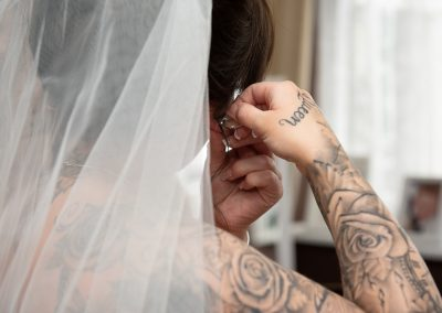 Bride putting on Jewellery for Harlow Wedding