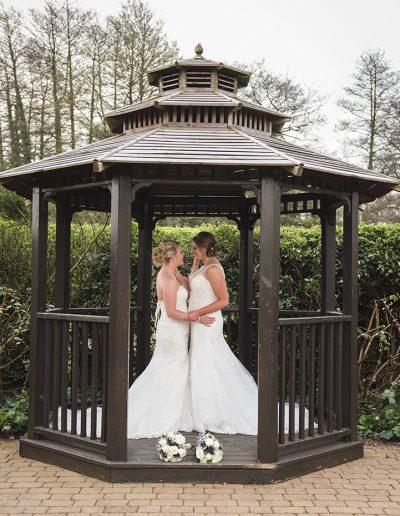 Bridal couples portrait of two brides under wooden gazebo