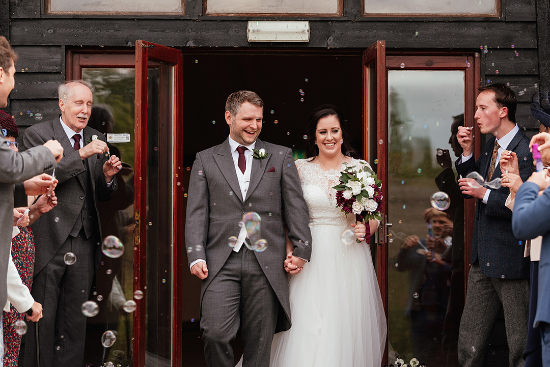 Bride and Groom walk through Bubbles Confetti Colville Hall Wedding Ceremony