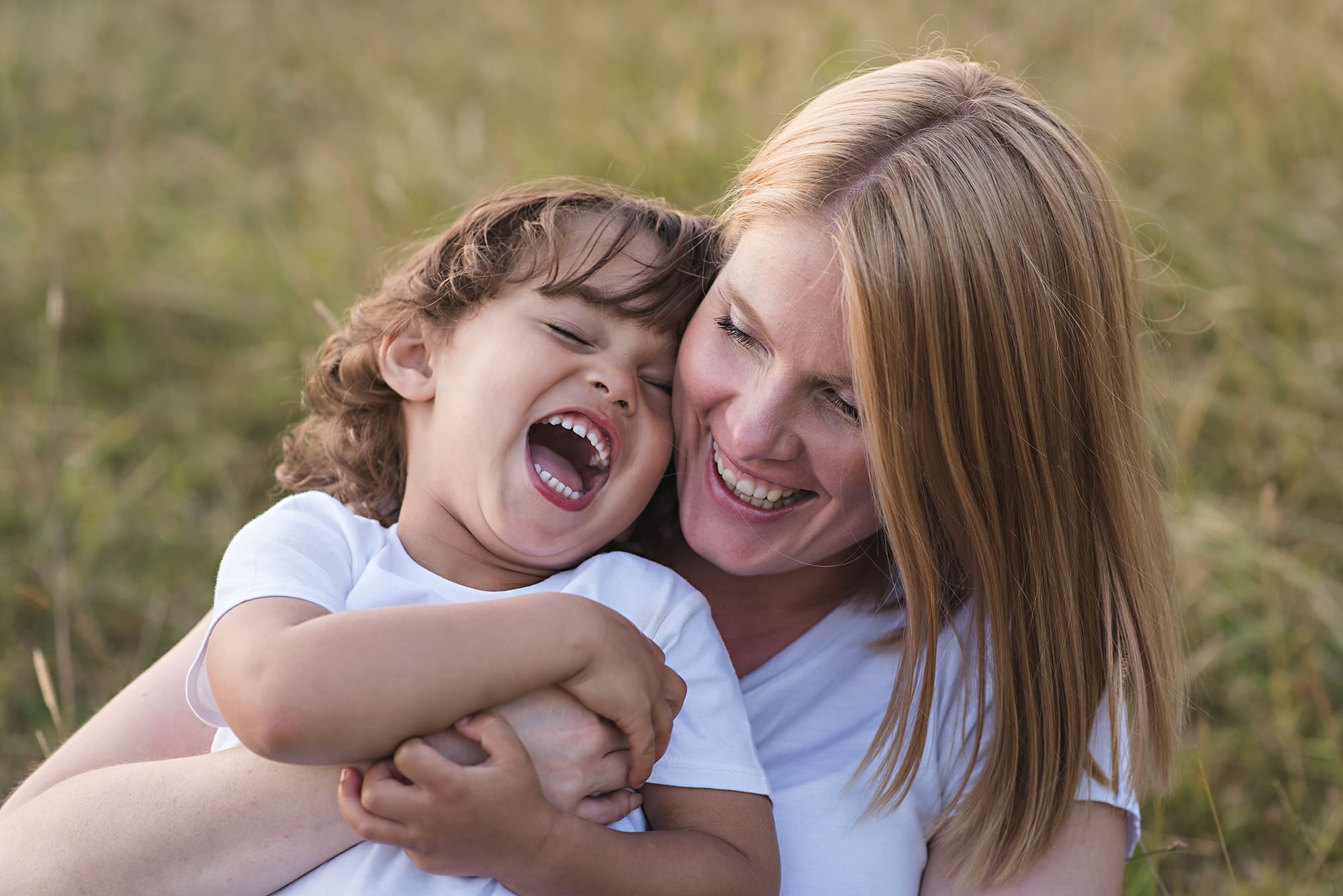 Natural family photographer, mum and son embrace and laugh together