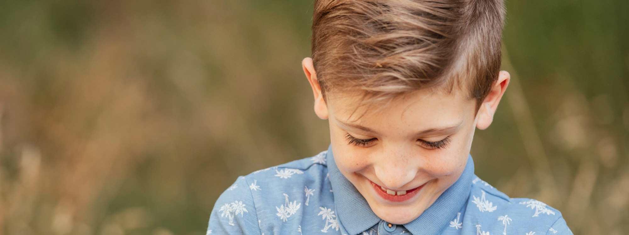 Boy Looking Down Smiling in Natural Family Photo Session Essex