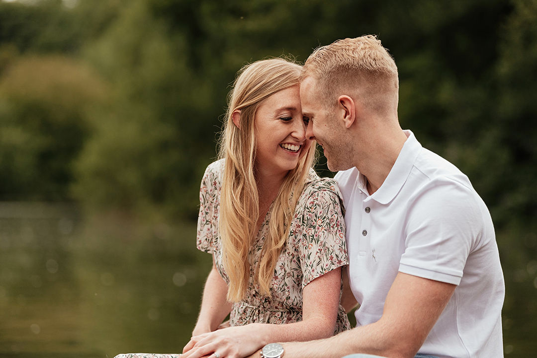 Couples sit head together by lake Candid Pre Wedding Photo Shoot Ideas Stanborough Lake