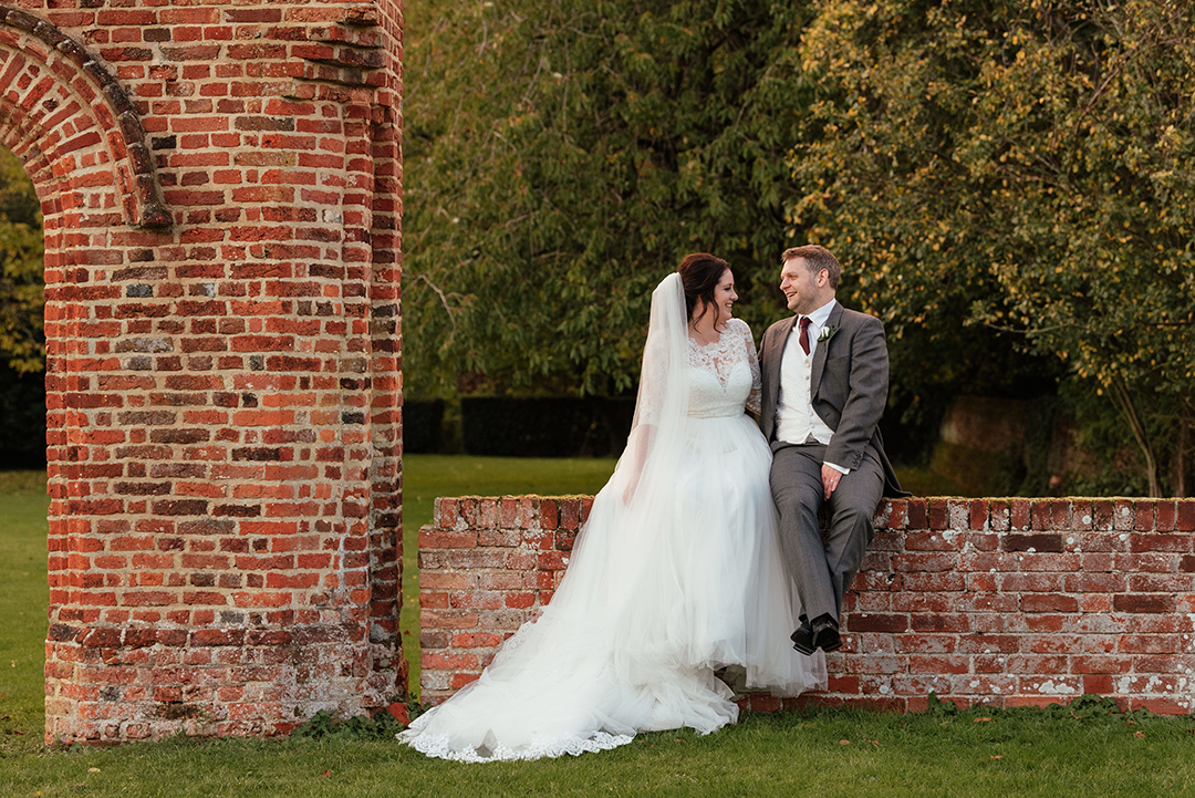 Couples Portraits sitting on wall by archway Colville Hall Wedding Photography