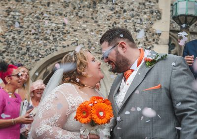 Couple kiss while confetti is thrown outside the church at St Nicholas at Wade