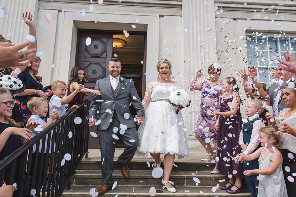 Essex wedding photographer captures Bride and groom walking down the steps while guest throw confetti