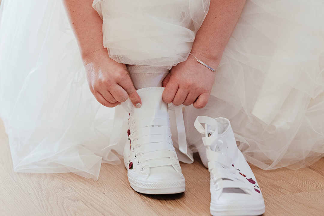Bride puts on Converse wedding shoes