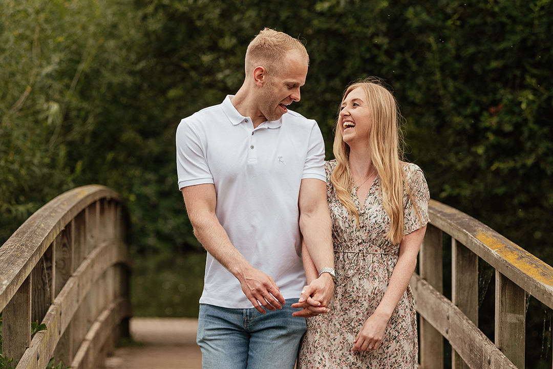 Couple Walk towards camera bumping hips Engagement Photos at Stanborough Lake