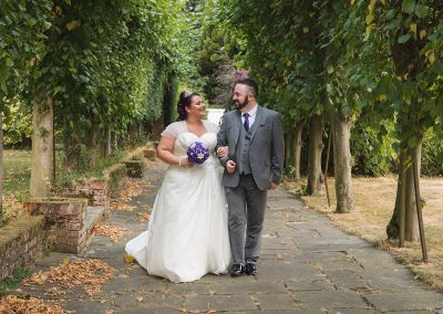 Couple walk towards camera in Parklands Quendon Hall gardens