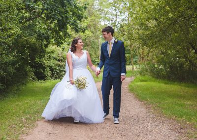 Bride and Groom share natural moment as they walk towards the camera