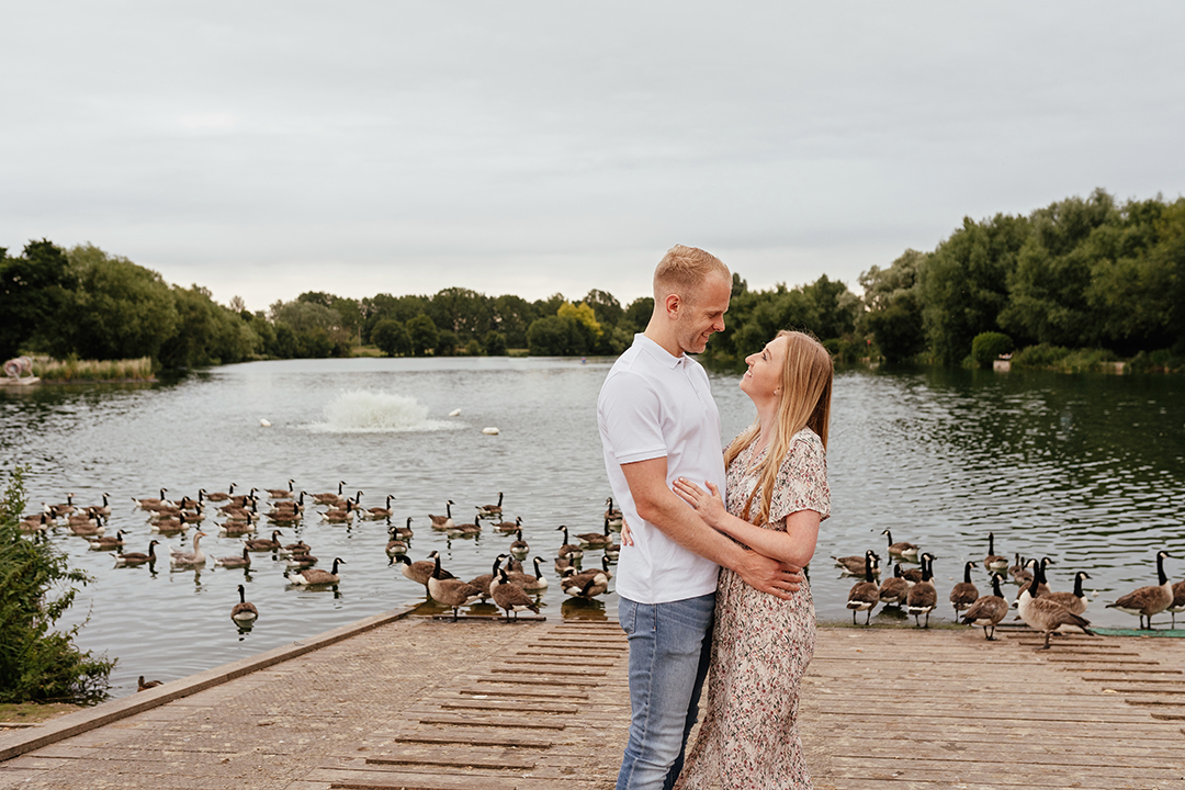 Couple embrace with geese and lake behind them Pre Wedding Photos at Stanborough Lake