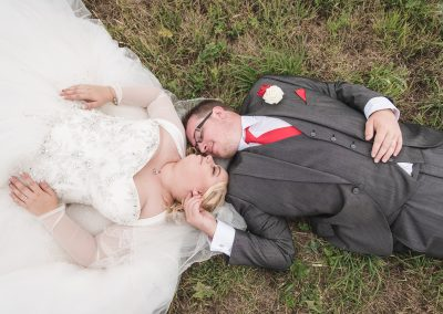 Bride and Groom lay in Grass for couples Photo at Crondon Park Essex