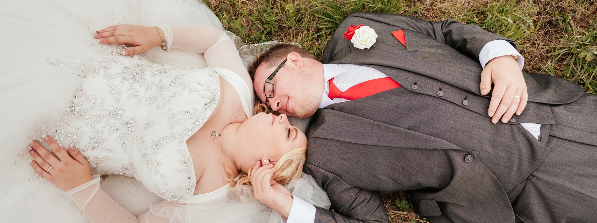 Couple lay together in grass at Crondon Park Wedding