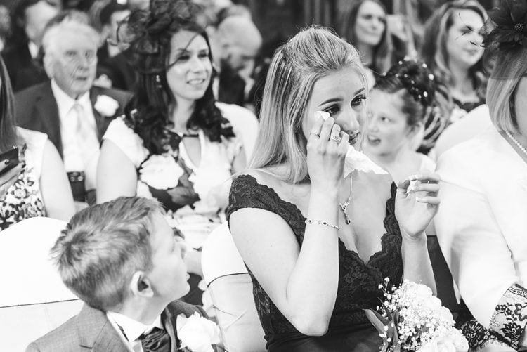 Essex wedding photographer captures Bride's sister wipes tear during emotional wedding ceremony