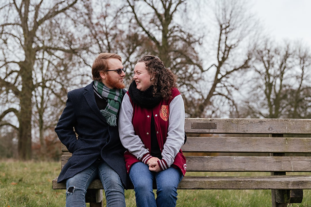 Couple sit closely together in Country park photo shoot