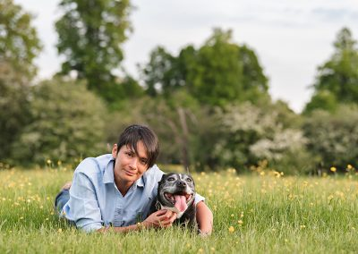 Dog and owner laying in buttercups for photo shoot
