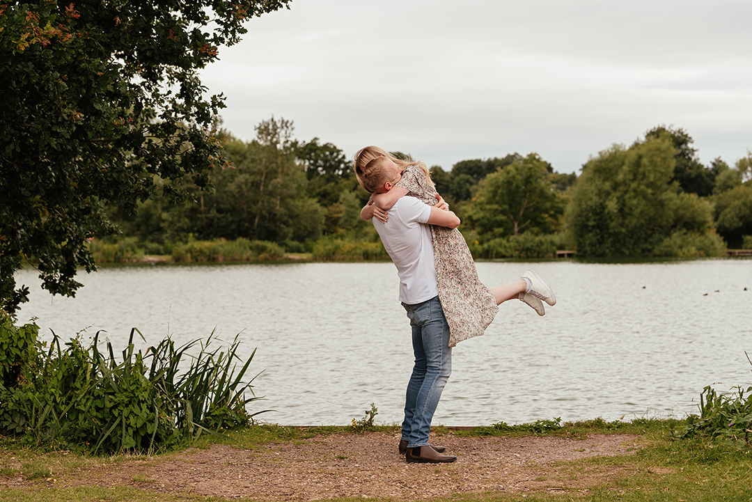 Groom to be lifts his bride to be in the air and embraces in Engagement Photography at Stanborough Lake