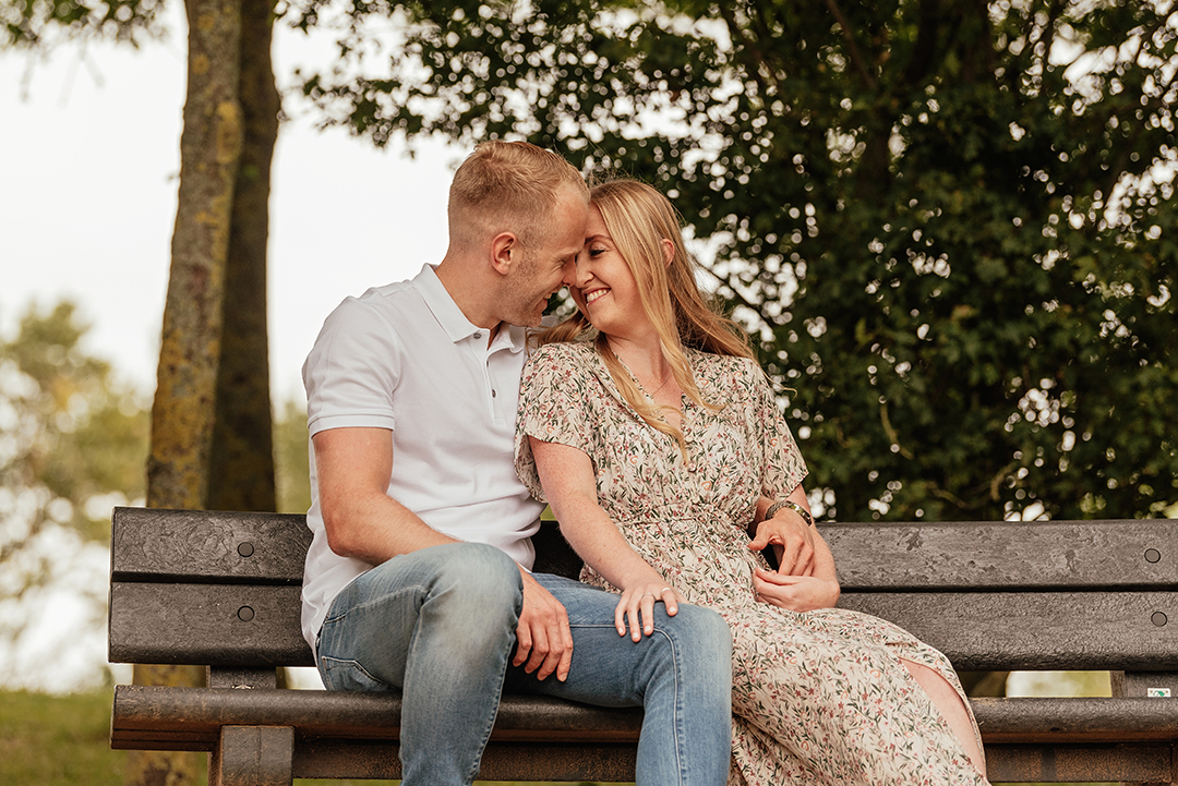 Couple sit together in embrace on bench in Engagement Photoshoot at Stanborough Lake