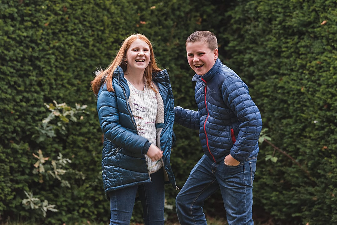 Brother and sister laughing together in natural moment