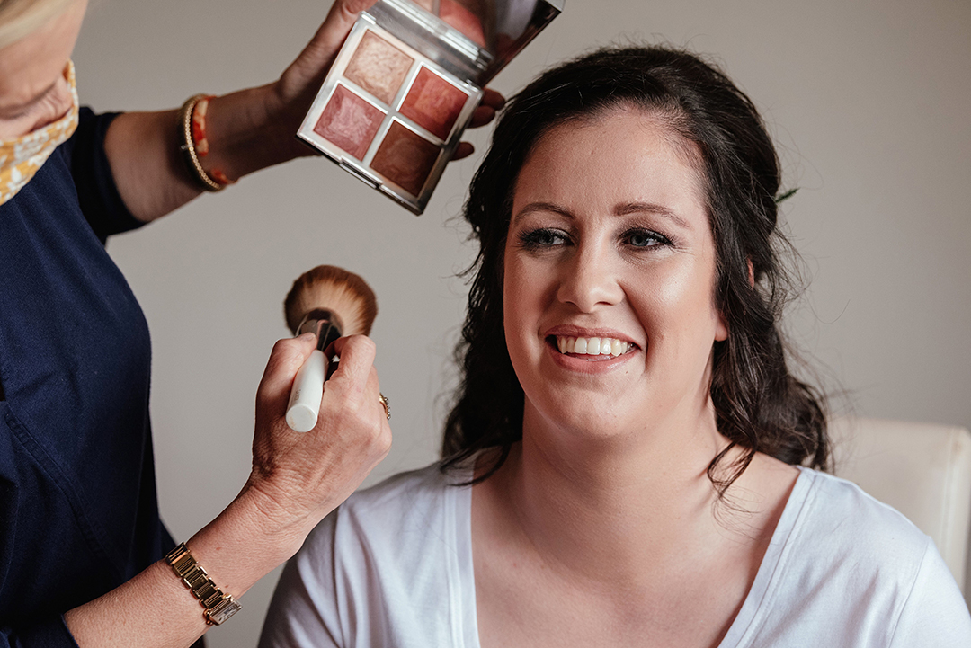 Adding final Make up touches as bride smiles at Colville Hall