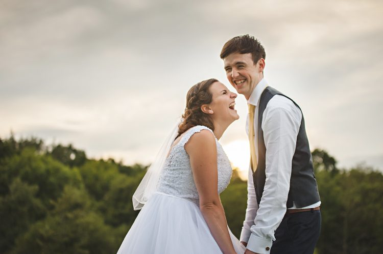 Essex Wedding photographer captures Couple at Sunset Holding Hands and Laughing