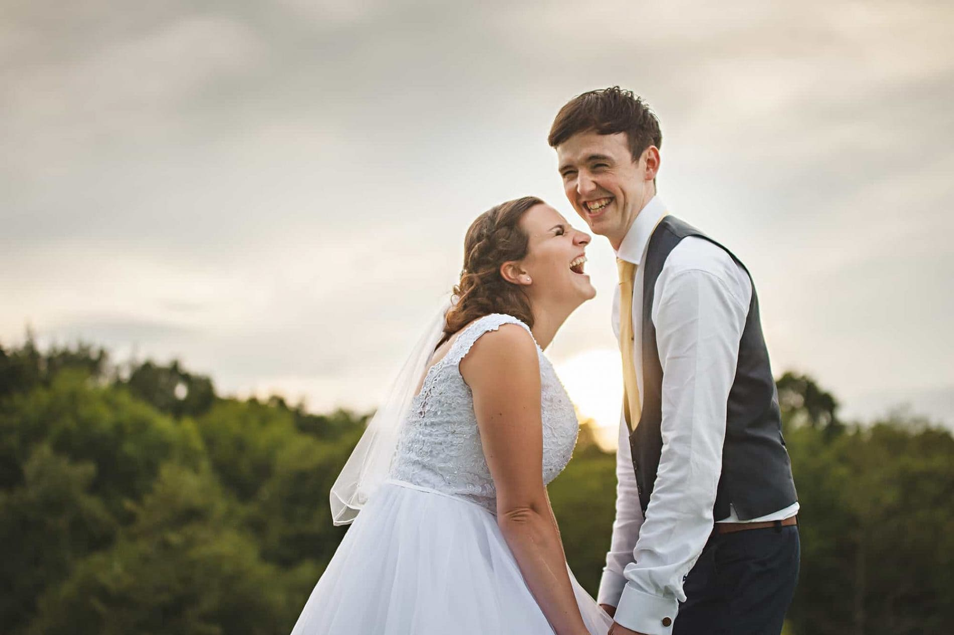 Essex wedding photography - couple laughing together and holding hands at sunset