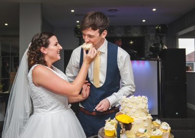 Bride feeds her new groom some wedding cake