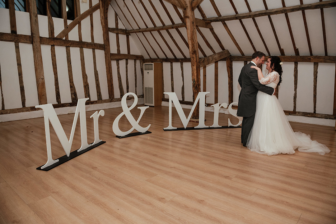 Couple close together during First Dance with Mr and Mrs sign at Colville Hall