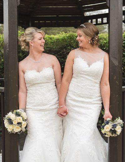 Natural portrait of two brides under wooden gazebo