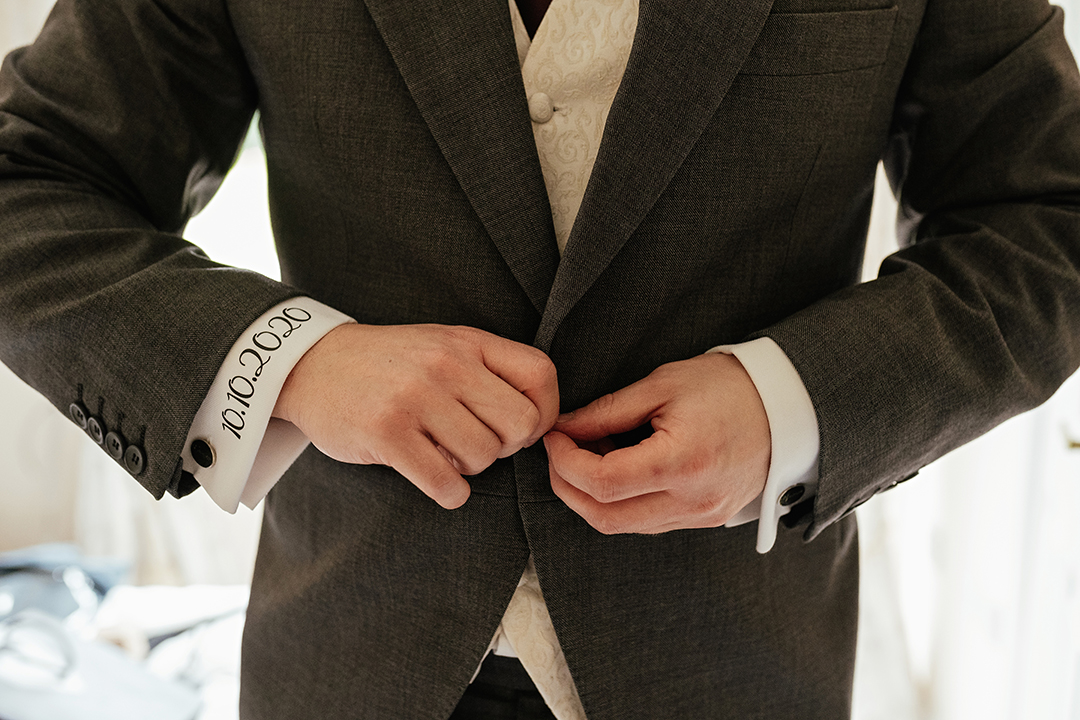 Groom Buttoning Suit Jacket at Colville Hall
