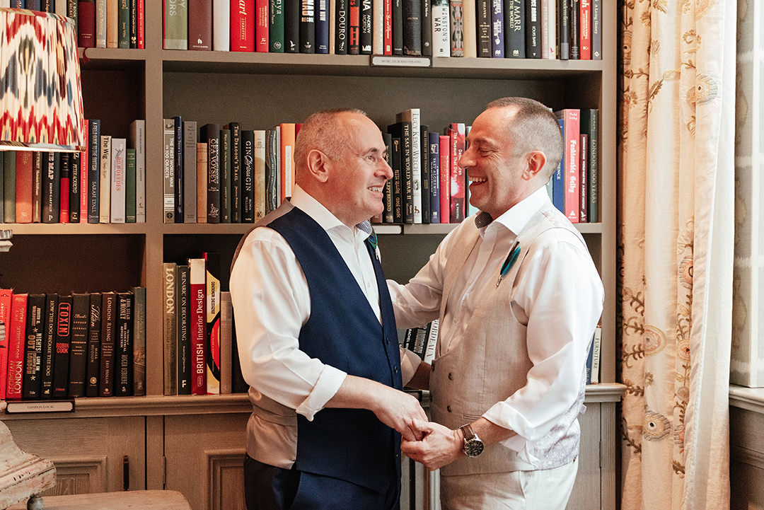 Grooms Embrace in Front of Bookshelves Ham Yard Hotel Library