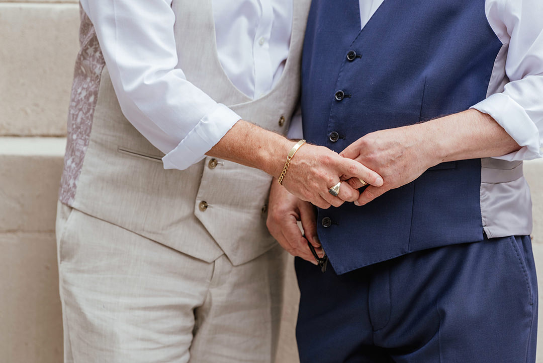 Grooms Hold Hands outside Old Marylebone Town Hall