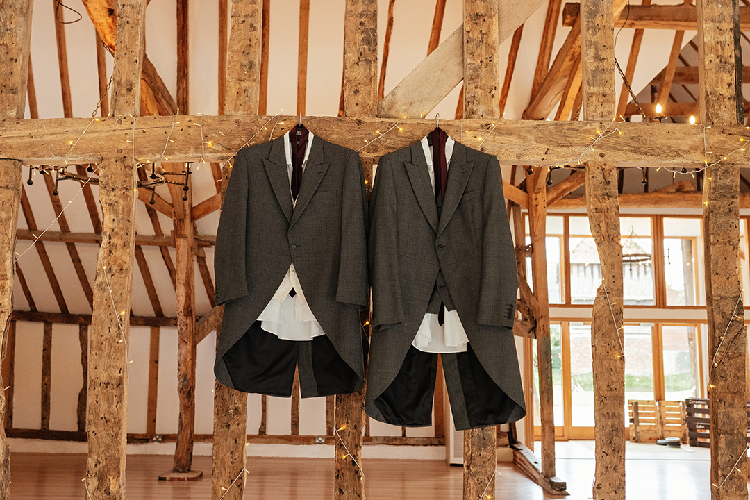 Grooms Suits Hanging on Wooden Beam in Mill Pond Barn Colville Hall