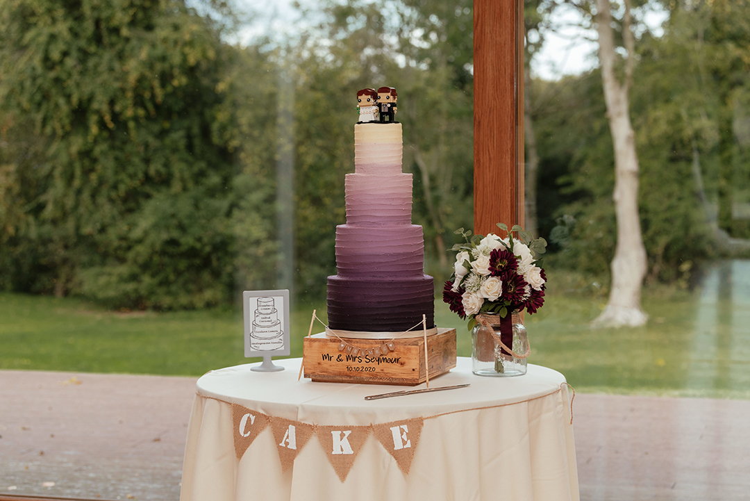 Purple gradient wedding cake on table by window at Colville Hall