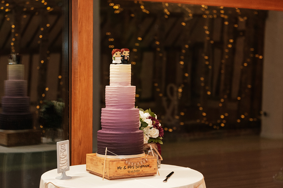 Purple gradient wedding cake on table by window at night at Colville Hall