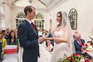 Essex wedding photographer Couple exchange rings at Hunton Park wedding Ceremony