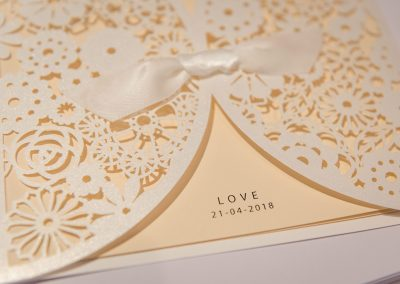 Laser cut paper wedding invatations with the word love and the wedding date