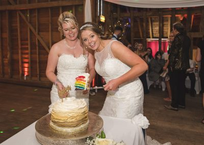 Bride holds up slice of cake with rainbow slices
