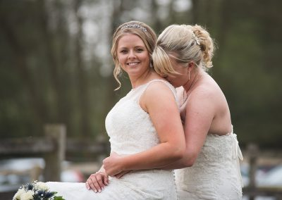 Gorgeous natural portrait of two brides embracing while sat on bride at Tewin Bury Farm Hotel