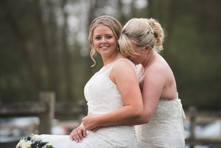 Essex wedding photographer captures Gorgeous natural portrait of two brides embracing while sat on bride at Tewin Bury Farm Hotel