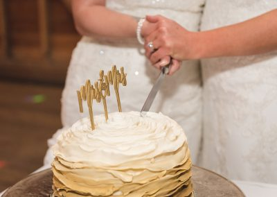 Two brides cut Mrs and Mrs cake topped wedding cake