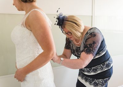 Mother of the bride helps her fasten wedding gown