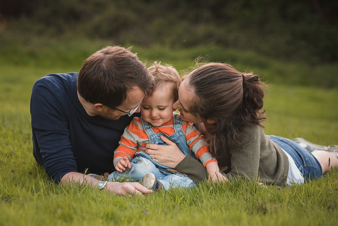 Family lay in grass and share candid moment