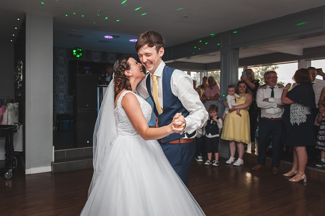 Couple smiling and laughing together for first dance by Essex photographer