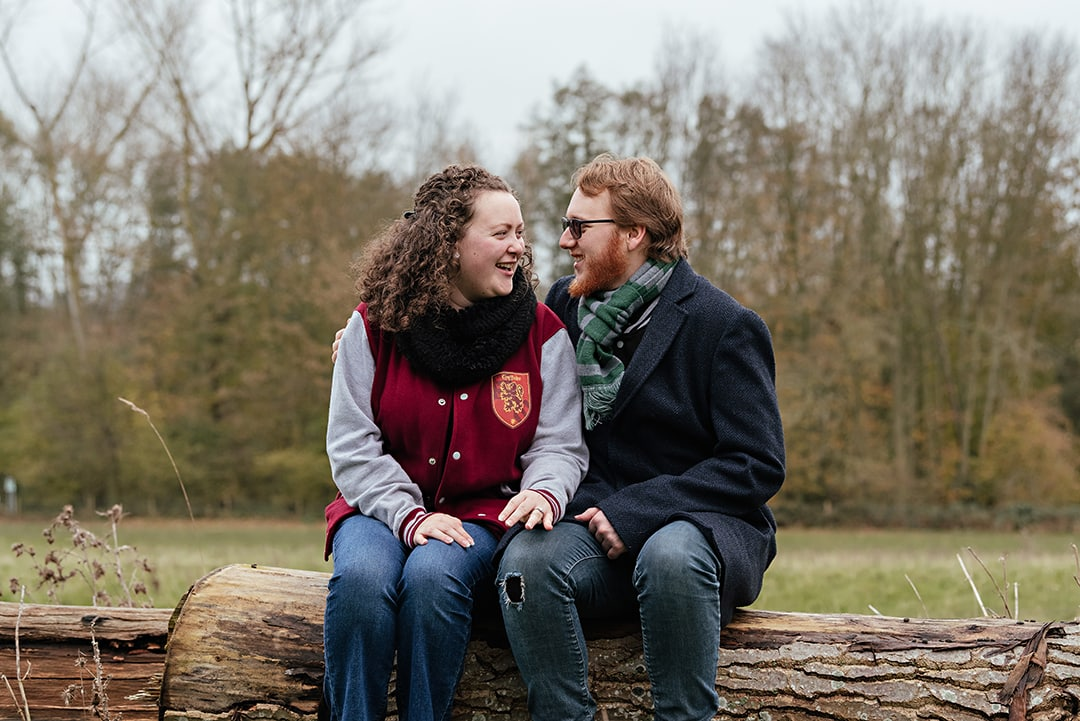 Sitting on a log nice and close together, couple look to each other
