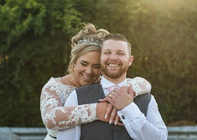 Natural relaxed couples shot of bride hugging her groom from behind