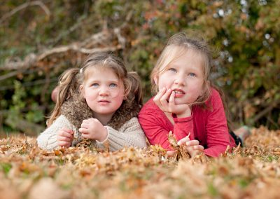 Girls laying in autumn leaves in photo session in Harlow, Essex